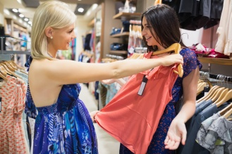 Woman holding shirt up to friend in clothes store